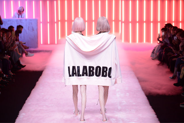 Two models share a giant hoodie as they walk down the runway at the Lalabobo show during China Fashion Week in Beijing, China on March 28, 2017. (Photo by Imaginechina/Rex Features/Shutterstock)