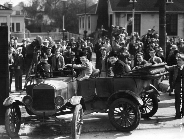 Spectators gather to watch the filming of 'County Hospital' on location in Los Angeles. In the foreground are the Hal Roach comedians and stars of the production, Stan Laurel (1890 - 1965) and Oliver Hardy (1892 - 1957), 1924