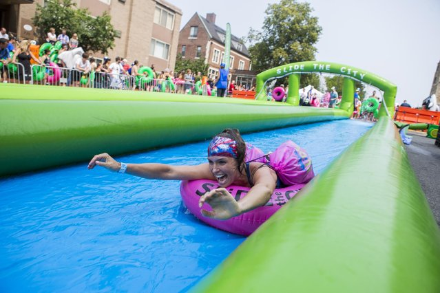 In this July 4, 2015, photo, a woman smiles as she slides along South State Street on the University of Michigan campus during Slide the City, in Ann Arbor, Mich. (Photo by Dominic Valente/Detroit News via AP Photo)