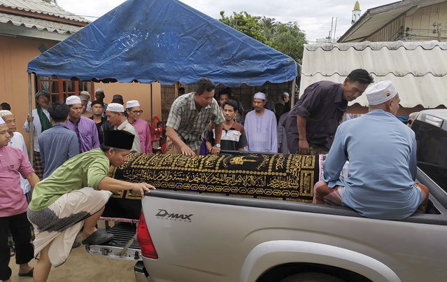 In this Sunday, August 25, 2019, photo, Muslim villagers load the body of Abdulloh Esomuso on the truck to a cemetery in Pattani southern of Thailand. Esomuso was arrested July 20, 2019, on suspicion of being a separatist insurgent and found unconscious the next day in his cell at an army base in the deep south province of Pattani. He died on Sunday, Aug. 25, with his family and human rights groups seeking an investigation of whether his death was due to torture. (Photo by AP Photo/Stringer)