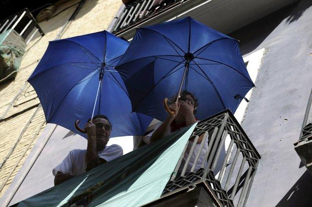 People hold umbrellas while watching a procession in honour of San Fermin at the San Fermin festival in Pamplona, northern Spain, July 7, 2015. (Photo by Eloy Alonso/Reuters)