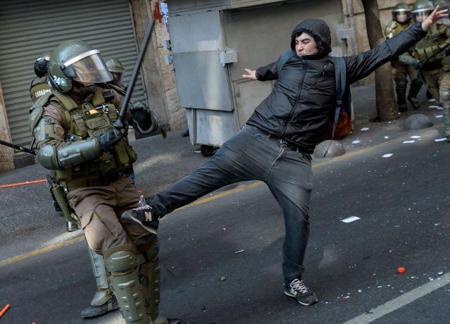 """Demonstrators clash with riot police during a rally called by Chilean Human Rights organization """"Detained and Disappeared People"""" to commemorate the 46th anniversary of the military coup led by General Augusto Pinochet that deposed President Salvador Allende, in Santiago, on September 8, 2019. Next September 11 marks the 46th anniversary of the coup. (Photo by Martin Bernetti/AFP Photo)"""