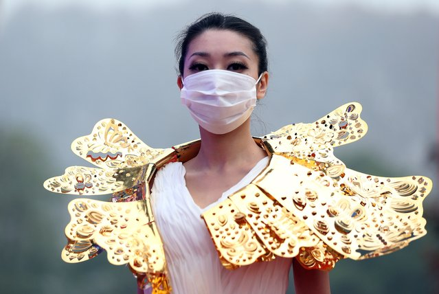 This picture taken on December 7, 2013 shows a model wearing a surgical mask as she parades a collection of gold jewelleries at a park in Nanjing, east China's Jiangsu province. Cities across China have been hit by intense air pollution especially in winter months, much of it caused by emissions from coal-burning power stations, with PM 2.5 levels reaching as high as 40 times WHO limits, while the country's rapid urbanisation, dramatic economic development and climatic factors, further worsen the condition. (Photo by AFP Photo)