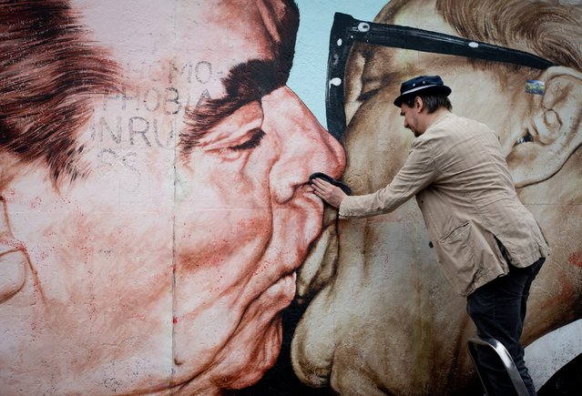 Russian artist Dimitri Vrubel cleans his painting depicting Soviet leader Leonid Brezhnev kissing his East German counterpart Erich Honecker at the East Side Gallery in Berlin, Germany, 27 April 2014. Several artists along with Berlin residents and tourists cleaned paintings of the 1.3 km long section of the Berlin Wall. (Photo by Kay Nietfeld/EPA)