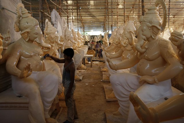 An Indian man paints idols of elephant headed Hindu god Ganesha being prepared ahead of the Ganesh Chaturti festival in Mumbai, India, Thursday, July 9, 2015. The idols will be immersed in the Arabian Sea after they are worshipped during the festival that falls in September. (Photo by Rajanish Kakade/AP Photo)