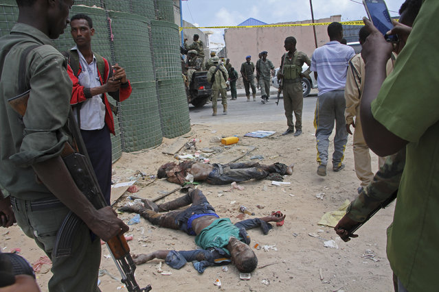 Somali soldiers stand near the dead bodies of two Al-shabab fighter who were killed during clashes with security forces in Mogadishu, Somalia, Sunday, April, 16, 2017. At least two Al-Shabaab militants were killed in a mortar attack in Somali capital Mogadishu on Sunday, a government official confirmed. At least three mortars landed into a residential area in Wadajir district which is near the heavily guarded Mogadishu airport, which has seen mortar attacks by the militants in the past few days. (Photo by Farah Abdi Warsameh/AP Photo)