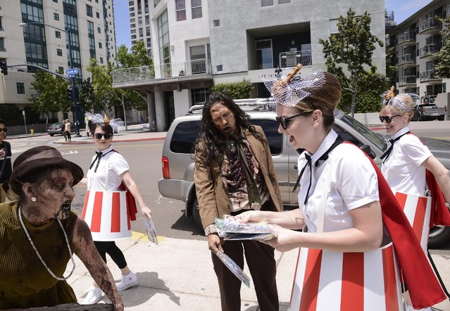KFC distributes limited edition Colonel Sanders comic books to fans at San Diego's biggest comic convention on Friday, July 10, 2015 in San Diego, Calif. (Photo by Dan Steinberg/Invision for KFC/AP Images)