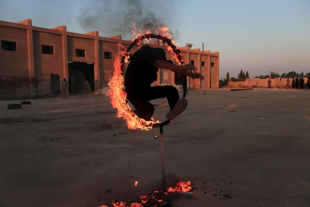 A rebel fighter jumps through a fire loop as he demonstrates his skill during a military display as part of a graduation ceremony at a camp in eastern al-Ghouta, near Damascus, Syria July 12, 2015. The newly graduated rebel fighters, who went through military training, will join the the Free Syrian Army's Al Rahman legion. (Photo by Bassam Khabieh/Reuters)