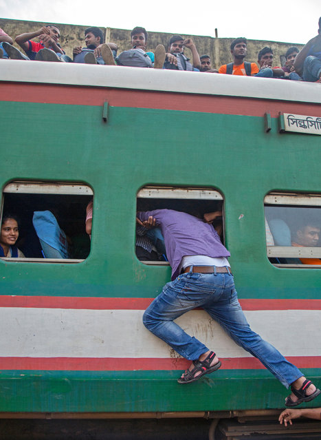 A man try to enter into an overcrowded train as he travel to celebrate Eid with family in the villages, at the Kamlapur Railway Station in Dhaka, Bangladesh, 03 June 2019. (Photo by Monirul Alam/EPA/EFE)