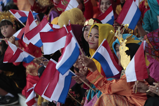 School children wave Indonesian and Dutch national flags during the welcoming ceremony of Dutch Prime Minister Mark Rutte at the presidential palace in Bogor, West Java, Indonesia, Monday, October 7, 2019. (Photo by Dita Alangkara/AP Photo)