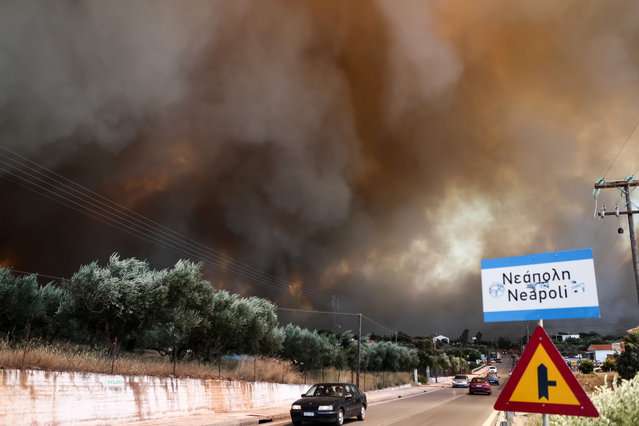 A wild fire burns over the town of Neapoli, southern Greece, Friday, July 17, 2015. (Photo by Vassilis Konstantopoulos/InTime News via AP Photo)