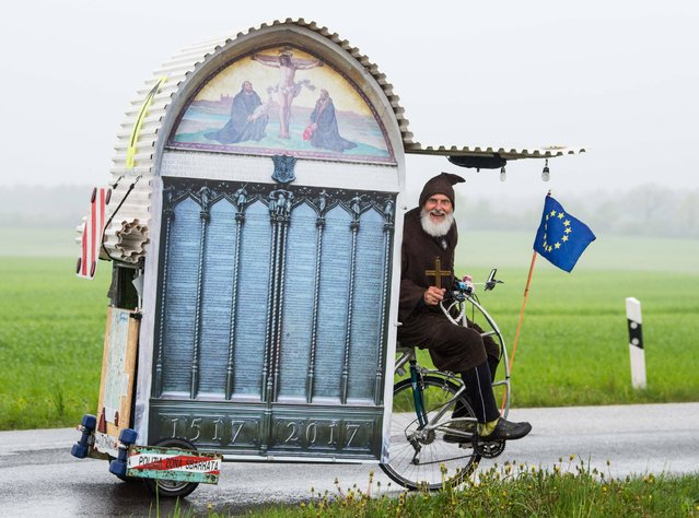 "German bicycle enthousiast Dieter ""Didi"" Senft presents his latest creation, a self-designed ""Luther-Mobil"", on a road near Sieversdorf, northeastern Germany, on May 4, 2017. The bike features the porch of Wittenberg's All Saint's Church, where German church reformer Martin Luther is reported as having posted his Ninety-five Theses against abusive practices by preachers selling plenary indulgences 500 years ago. (Photo by Patrick Pleul/AFP Photo/DPA)"