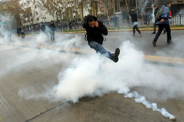 Students clash with riot police during a march held to protest the slow pace of educational reform, in Santiago, on May 26, 2016. (Photo by Claudio Reyes/AFP Photo)