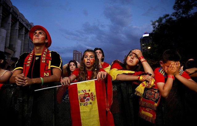 Spanish soccer fans in Madrid watch on a giant display as Netherlands beats Spain in a World Cup match, on June 13, 2014. (Photo by Daniel Ochoa de Olza/Associated Press)