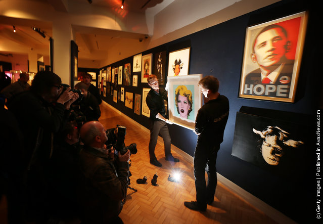 Employees George Foren (L) and Matthew Fancy hold Banksy's 'Kate Moss 2005'  at Bonhams