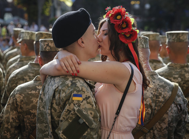 A Ukrainian serviceman gives his girlfriend a kiss at Kiev's Independence Square, Ukraine, 24 August 2015, before a march on the occasion of Independence Day. Ukrainians marked the 24th anniversary of Ukraine's independence from the Soviet Union in 1991. (Photo by Roman Pilipey/EPA)