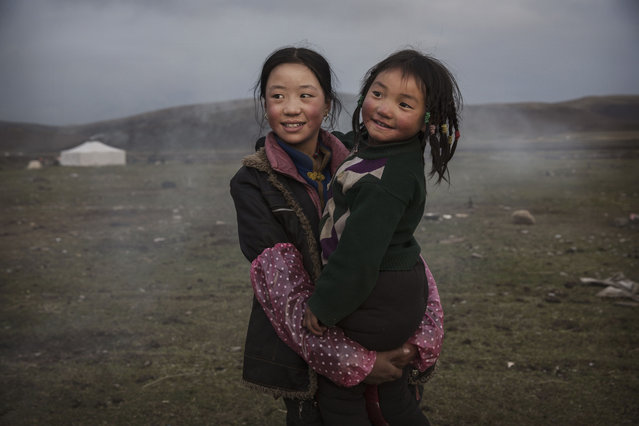 A young  Tibetan nomad girl holds her sister at a temporary camp for picking cordycep fungus on May 22, 2016 on the Tibetan Plateau near Sershul in the Garze Tibetan Autonomous Prefecture of Sichuan province. (Photo by Kevin Frayer/Getty Images)