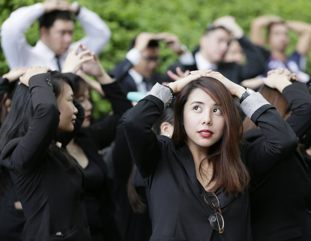 Hotel and office employees cover their heads as they take part in a Metropolitan Manila-wide earthquake drill which was designed to boost preparedness in the country Thursday, July 30, 2015 at the financial district of Makati city east of Manila, Philippines. (Photo by Bullit Marquez/AP Photo)