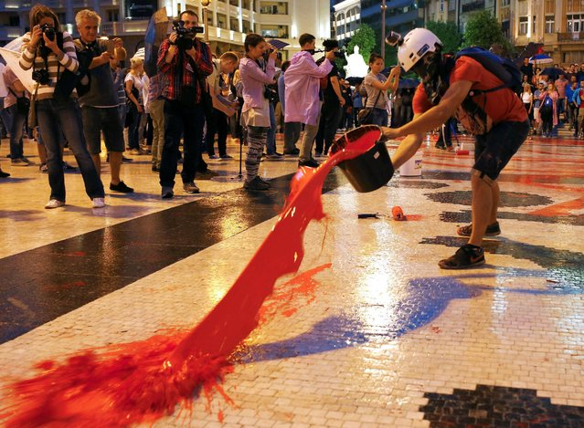 Protesters spill buckets of color paint during a protest against the government, at Central Square in Skopje, Macedonia June 6, 2016. (Photo by Ognen Teofilovski/Reuters)