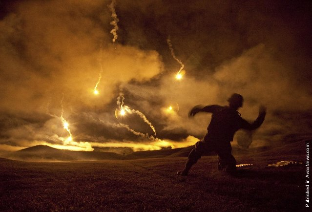 Staff Sgt. Angel Alvarez assigned to the Warrior Training Center at Fort Lee, Va., cocks back to throw a pyrotechnic grenade simulator into the sky during a night fire event for the 2011 Department of the Army Best Warrior Competition. During the event, competitors fired from the prone supported and prone unsupported firing positions while pyrotechnics exploded all around them