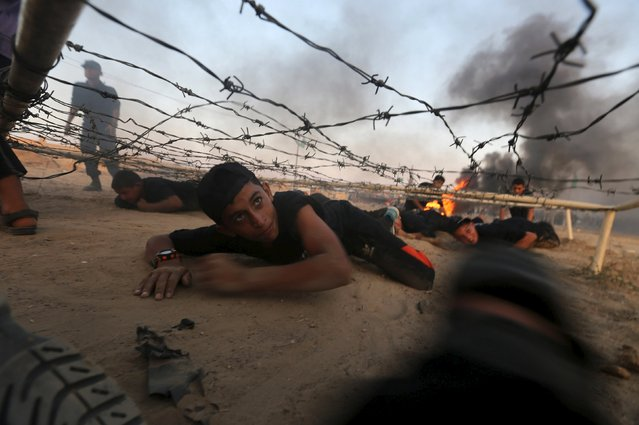 Young Palestinians crawl under an obstacle during a military-style exercise at Liberation Youths summer camp, organised by the Hamas movement, in Rafah in the southern Gaza Strip, August 1, 2015. (Photo by Ibraheem Abu Mustafa/Reuters)