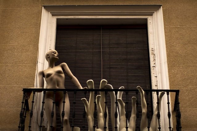 Mannequins stand on a balcony in the center of Madrid, Spain, on June 22, 2014. (Photo by Andres Kudacki/Associated Press)