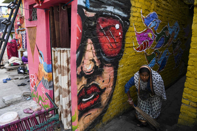 "A woman sweeps an alleyway adorned with murals painted by artists from ""Delhi Street Art"" group at the Raghubir Nagar slum in New Delhi on December 2, 2019. (Photo by Sajjad Hussain/AFP Photo)"