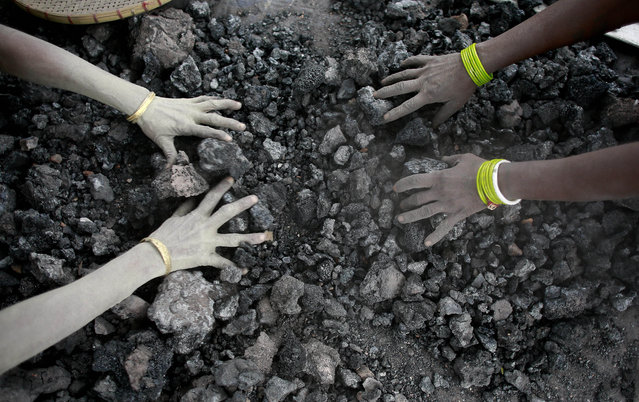 In this Monday, Dec. 14, 2015, photo, Indian women use bare hands to pick reusable pieces from heaps of used coal discarded by a carbon factory in Gauhati, India. The world's biggest coal users – China, the United States and India – have boosted coal mining in 2017, in an abrupt departure from last year's record global decline for the heavily polluting fuel and a setback to efforts to rein in climate change emissions. (Photo by Anupam Nath/AP Photo)