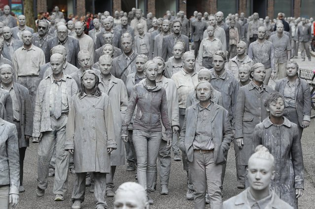 Performance artists covered in clay to look like zombies walk trance-like through the city center on July 5, 2017 in Hamburg, Germany. In a two-hour show hundreds of actors took part in a creative public appeal for more humanity and self-responsibility ahead of the upcoming G20 summit. The G20 economic summit takes place in Hamburg July 7-8. (Photo by Sean Gallup/Getty Images)