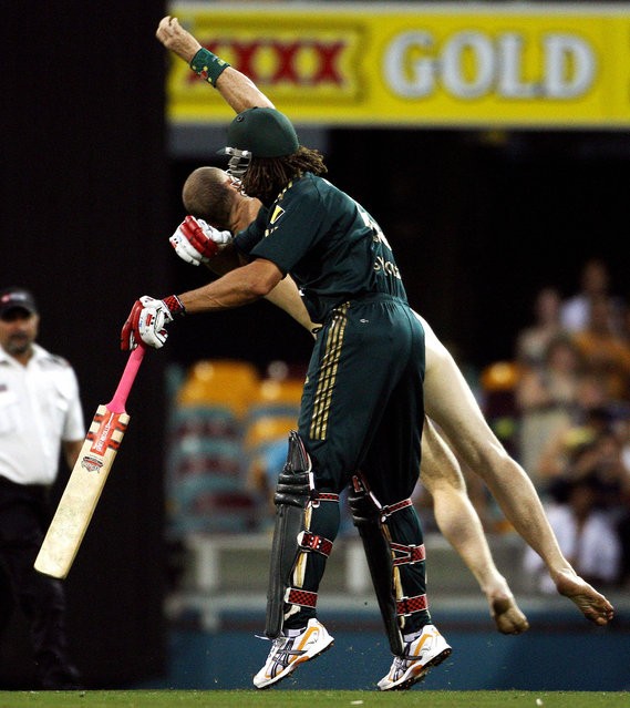 Australia's Andrew Symonds (front) clashes with a streaker (back) during the second final in the one-day triangular series cricket match in Brisbane on March 4, 2008. Australia are chasing India's total of 258. (Photo by Greg Wood/AFP Photo)