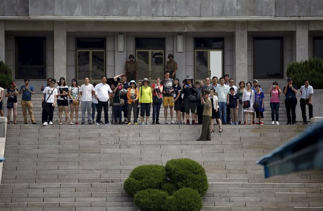 Tourists look towards the south side as they stand in the North Korean side of the truce village of Panmunjom in the demilitarised zone (DMZ) separating the two Koreas, South Korea, August 11, 2015. (Photo by Kim Hong-Ji/Reuters)