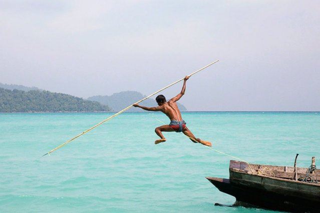The photos are on display in a free exhibition at the Royal Geographical Society in London, England from now until August 17, 2014. Seen here: A sea gypsy spear fishing on the Andaman Sea. (Photo by Cat Vinton)