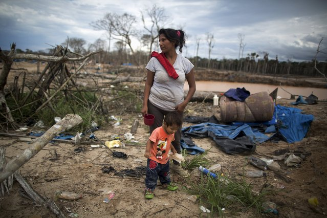 A woman and her child stand near debris after a police operation to destroy illegal gold mining camps in La Pampa, in the southern Amazon region of Madre de Dios, Peru August 11, 2015. (Photo by Sebastian Castaneda/Reuters)