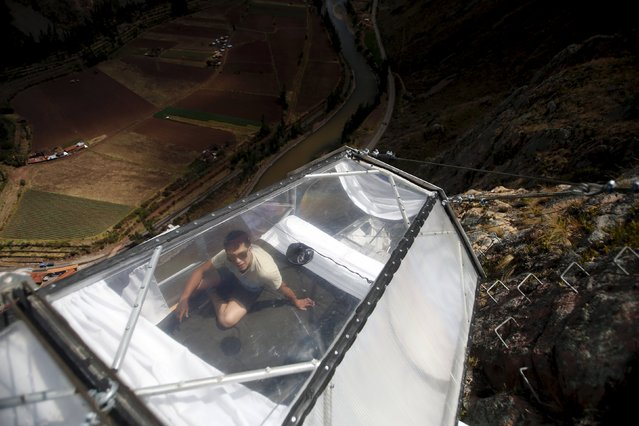 A guide rests as he cleans a sleeping pod at the Skylodge Adventure Suites in the Sacred Valley in Cuzco, Peru, August 14, 2015. (Photo by Pilar Olivares/Reuters)
