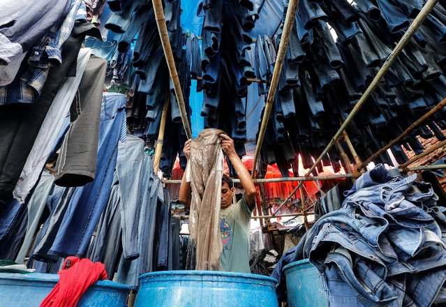 A man washes used trousers before they are sold in a second-hand clothing market in Mumbai, India, June 29, 2016. (Photo by Shailesh Andrade/Reuters)