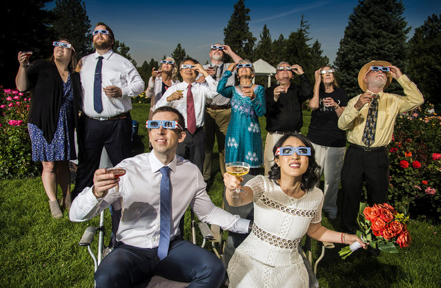 After their wedding ceremony, groom and bride, Nathan Mauger, Connie Young with family and friends, toast to the solar eclipse from the Rose Garden in Manito Park, Monday, August 21, 2017, in Spokane, Wash. (Photo by Colin Mulvany/The Spokesman-Review via AP Photo)