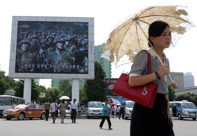 In this Friday, August 21, 2015 photo, a woman walks past a propaganda movie shown on a large screen in Pyongyang, North Korea. North Koreans are accustomed to being told they are on the brink of war with their southern neighbors and U.S. troops, and as talks with South Korea in the truce village of Panmunjom dragged on this weekend one had to look hard in the North Korean capital of Pyongyang to find signs of a brewing crisis. (Photo by Dita Alangkara/AP Photo)