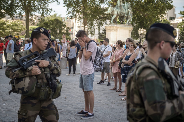 French soldiers patrol in front of the Notre Dame Cathedral during a minute of silence is held for the victims of the 14 July Nice attack, in Paris, France, 18 July 201. According to reports, at least 84 people died and many were wounded after a truck drove into the crowd on the famous Promenade des Anglais during celebrations of Bastille Day in Nice, late 14 July. (Photo by Christophe Petit Tesson/EPA)