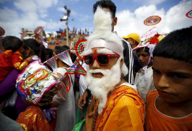 "A boy (C), dressed up as a holy man, participates in a parade to mark the Gaijatra festival ,also known as ""cow festival"", in Kathmandu, Nepal August 30, 2015. (Photo by Navesh Chitrakar/Reuters)"