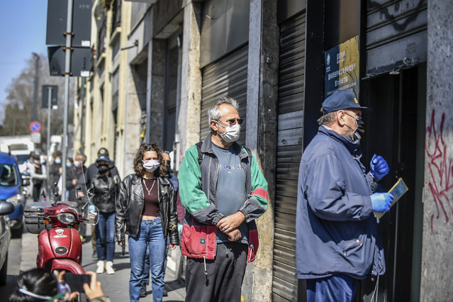 People line-up to get medical masks that are being distributed by the Chinese state-owned State Grid electrical company, at Milan's Chinatown neighborhood, Italy, Monday, April 6, 2020. (Photo by Claudio Furlan/LaPresse via AP Photo)