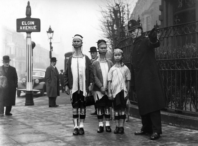 A policeman in London directing three giraffe necked women from Burma  along Elgin Avenue, London, 1935.   (Photo by General Photographic Agency)