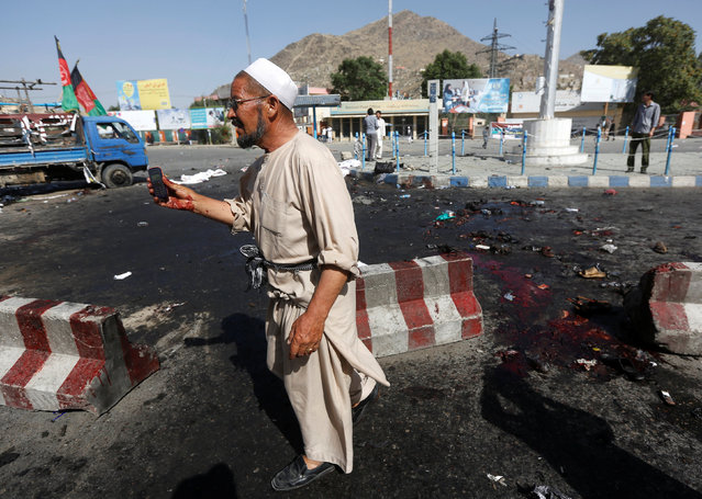 An Afghan man picks up a phone belonging to a victim after a suicide attack in Kabul, Afghanistan July 23, 2016. (Photo by Omar Sobhani/Reuters)