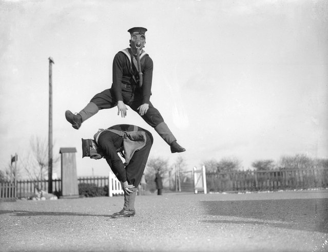 Able seamen at the Royal Navy Anti-Gas School at Tipnor, Portsmouth play leapfrog wearing gas masks, to accustom them to carrying out strenuous tasks in respirators. 22nd January 1934. (Photo by William Vanderson)