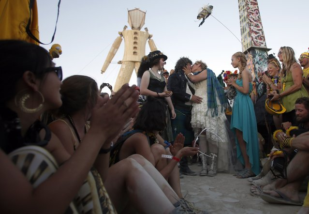 "Andrew Johnstone (standing, 2nd L), the designer of this year's man structure, marries Jeri Schneider during a ceremony at the Burning Man 2014 ""Caravansary"" arts and music festival in the Black Rock Desert of Nevada, August 27, 2014. (Photo by Jim Urquhart/Reuters)"