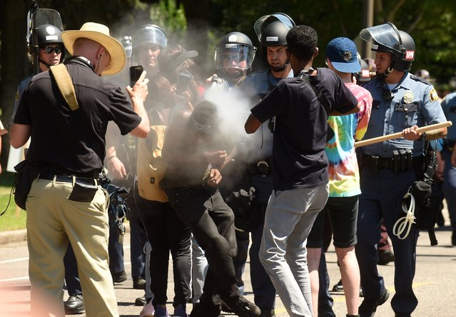 16-year old Tayvion Owens is sprayed with a substance by St. Paul police officers as they and protesters face off on Summit Ave., a block from the Governor's residence, in St. Paul, Minn. on Tuesday, July 26, 2016. Police have arrested an unknown number of protesters in front of the governor's mansion on St. Paul's Summit Avenue. Demonstrators have been camping outside the governor's residence since early July 7, a day after the shooting of Philando Castile, who was killed by a St. Anthony police officer during a traffic stop. (Photo by Scott Takushi/Pioneer Press via AP Photo)