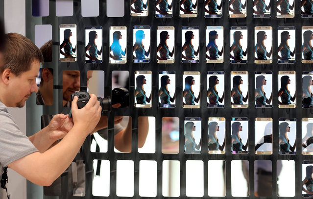 A journalist takes a photo of a presentation wall with Samsung Galaxy S6 Edge smartphones at International Consumer Electronics Fair IFA at the exhibition grounds in Berlin, Germany, 03 September 2015. The fair will take place from 4 to 9 September 2015. (Photo by Wolfgang Kumm/EPA)
