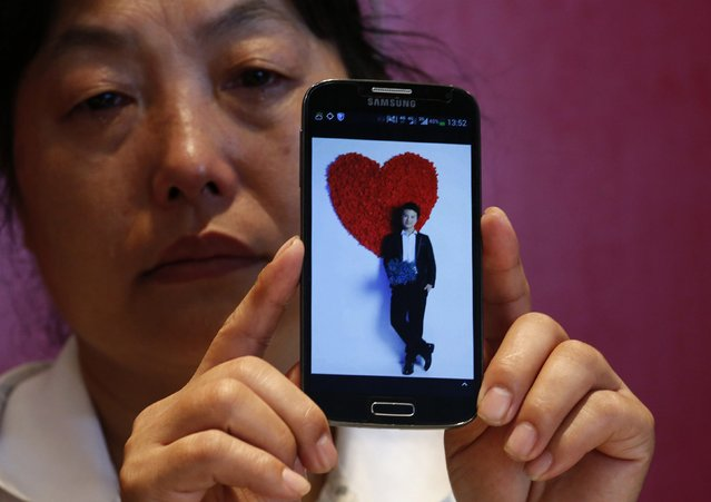 """Feng Xuehong, whose son Wang Houbin was onboard Malaysia Airlines Flight MH370 which disappeared on March 8, 2014 cries as she shows a picture of her son on her mobile phone during an interview with Reuters in Beijing July 18, 2014. In the last conversation with her son before the incident, the son said, """"Give me a hug, mom. Take care of yourself and I'll come back to see you soon"""". (Photo by Kim Kyung-Hoon/Reuters)"""
