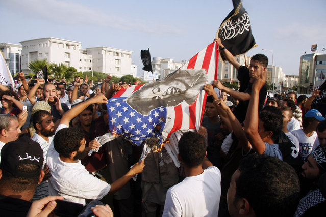 """Tunisian protesters lower and burn an American flag as they replace it with an Islamic flag during a demonstration against a film deemed offensive to Islam, outside the U.S. Embassy in Tunis on Sept. 12. A purported portrayal of the life of the Prophet Mohammed in the low-budget """"Innocence of Muslims"""" movie sparked protests all around the Middle East this week. (Photo by AFP)"""