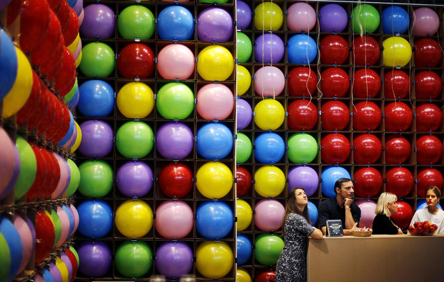 Employees of a publisher are surrounded by balloons as they wait for customers at the Book Fair in Frankfurt, Germany, Wednesday, October 11, 2017. (Photo by Michael Probst/AP Photo)