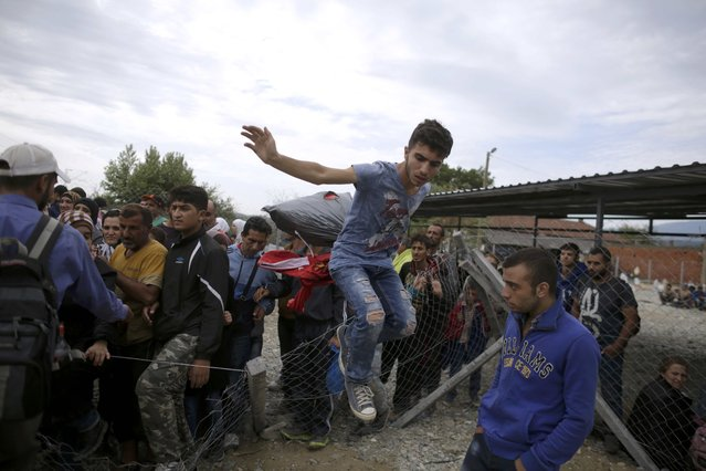 A migrant jumps over a fence as he tries to avoid police to get on a train near Gevgelija, Macedonia, September 7, 2015. (Photo by Stoyan Nenov/Reuters)